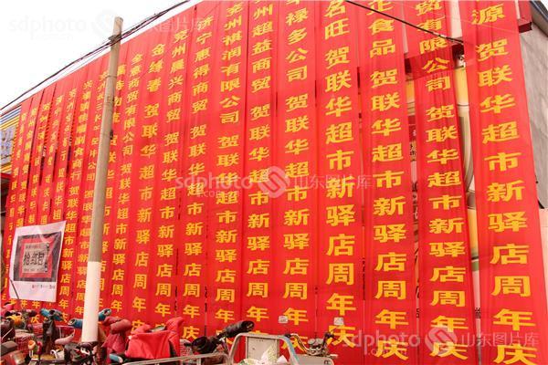 山东一购物中心举行店庆活动墙体被恭贺红条幅覆盖,如同红房子